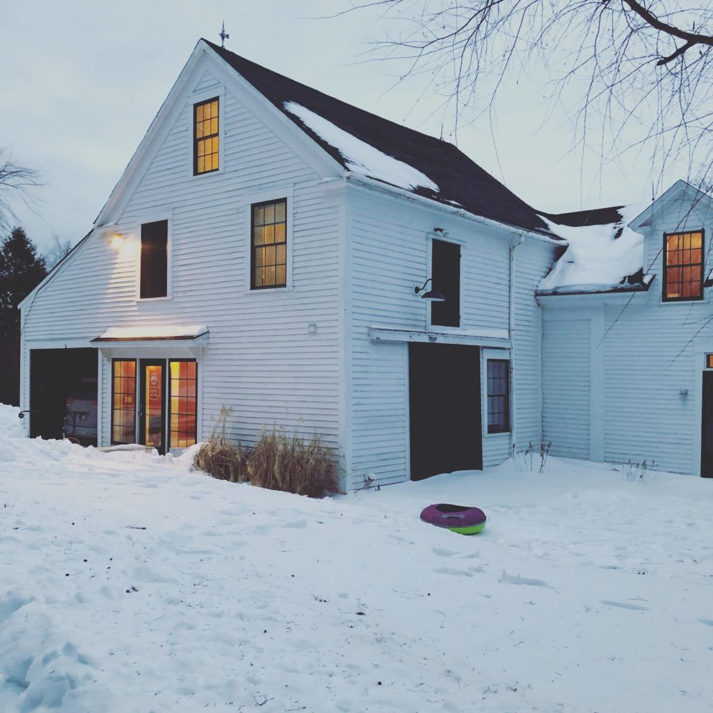 Snow covered house in Maine with Winter ambiance and light